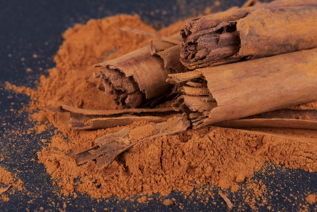 Sticks and ground ceylon cinnamon on dark surface