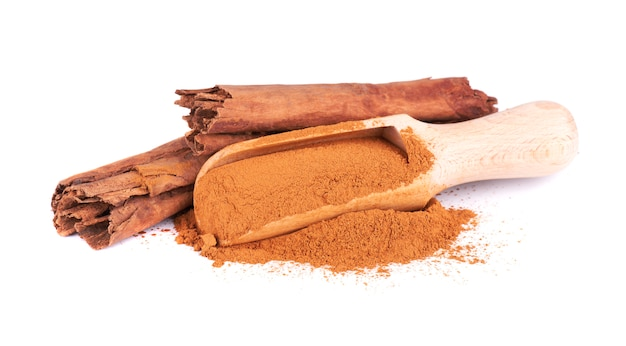 Sticks and ground ceylon cinnamon with wooden spoon, isolated on white.