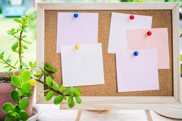 Sticky note on cork board with little tree,garden background