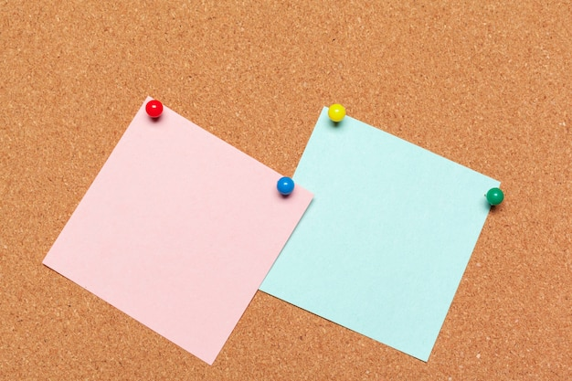 Sticky note pinned on cork board with thumbtacks