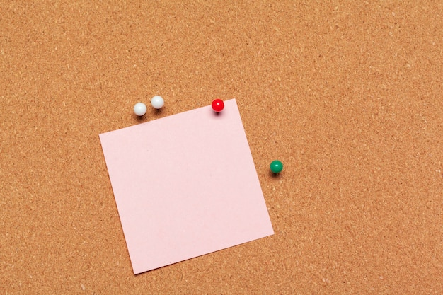 Sticky note pinned on corkboard with thumbtacks