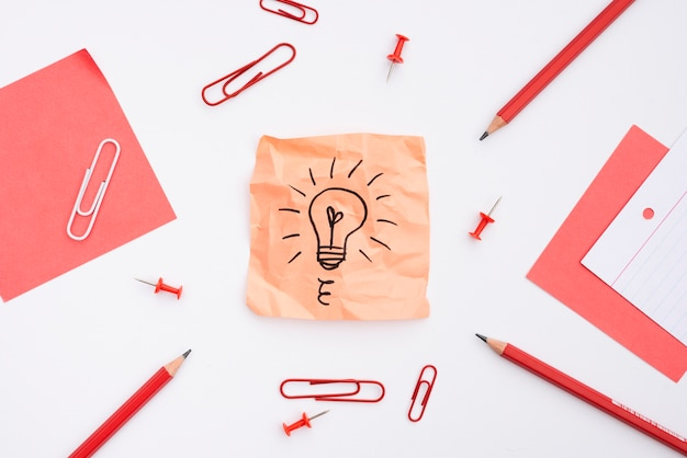 Sticky note with drawn light bulb and office supplies over white background