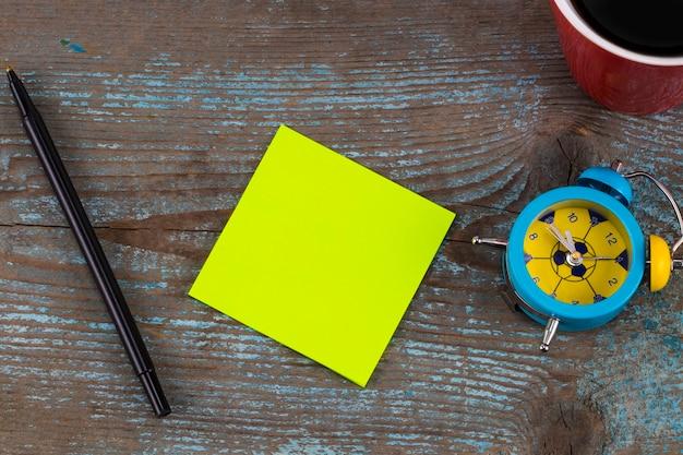 나무 배경에 텍스트와 커피 한 잔을 위한 빈 공간이 있는 스티커 메모. 새 해 해상도 개념입니다.