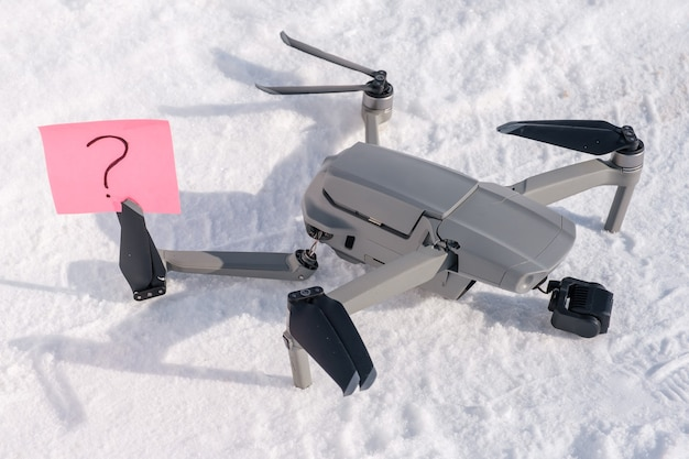 Sticky note with question mark in propeller blades of broken drone on snow
