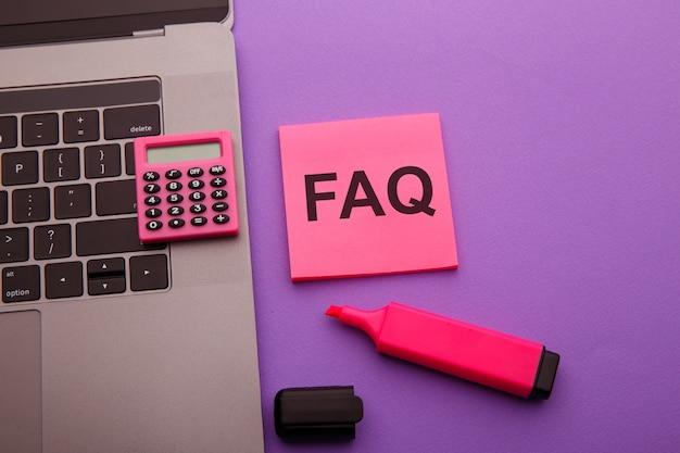 ピンクのテーブルにfaqという単語が付いた付箋。よくある質問の概念。