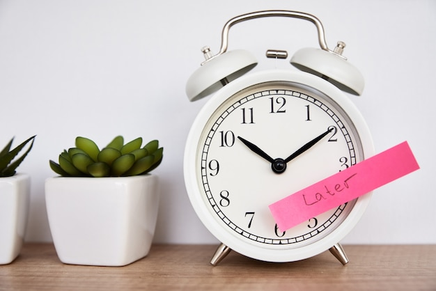 Sticky note with word later on the white alarm clock time