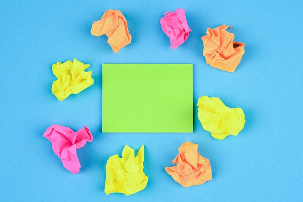 Sticky notes and crumpled paper balls on blue surface