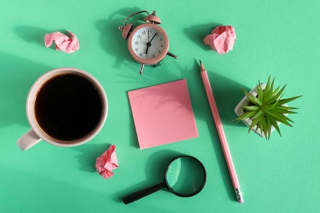 付箋紙、しわくちゃの紙、虫眼鏡、目覚まし時計、一杯のコーヒー