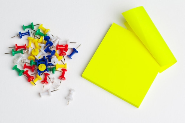 Sticky notes and pushpins on white . school .