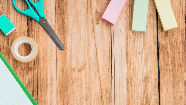 Sticky notes; scissor; tape and eraser on wooden table