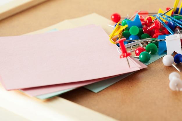 プッシュピンとコルクの空白の付箋。学校やビジネスのコンセプト