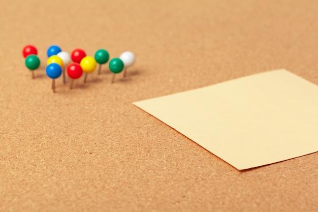 プッシュピンとコルクの空白の付箋。学校またはビジネス