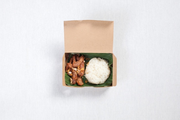 Sticky rice with fried pork put in a brown paper box, put on a white tablecloth, food box, thai food.