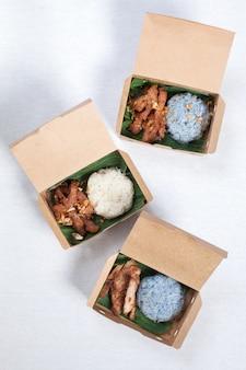 豚肉のグリルともち米と豚肉の炒め物を茶色の紙箱に入れ、白いテーブルクロス、フードボックス、タイ料理を入れます。