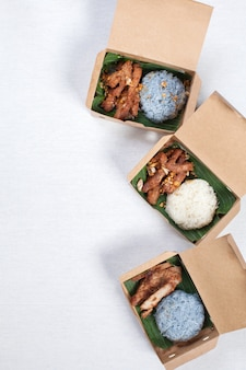 Sticky rice with grilled pork and fried pork put in a brown paper box, put on a white tablecloth, food box, thai food.