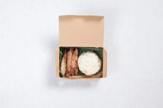 豚肉のもち米を茶色の紙箱に入れ、白いテーブルクロス、フードボックス、タイ料理を入れます。