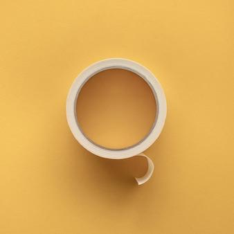 Рулон липкой ленты в желтом цвете фона