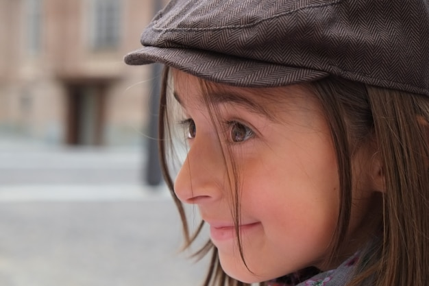 自然の中で微笑んでいるずんぐりした小さな白人の女の子。幸せそうな顔、エレガントな帽子と茶色の髪。