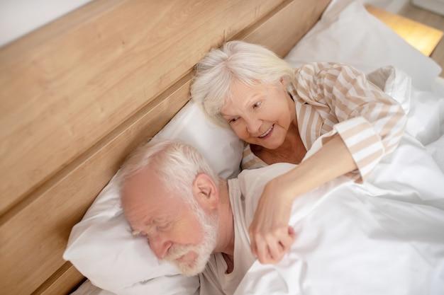 まだ恋をしています。眠っている夫を抱き締める白髪の老婆