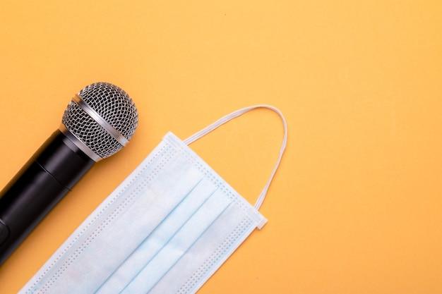 Все еще продолжайте носить маску, пока говорите. вид сверху на новый профилактический защитный микрофон и беспроводной микрофон черного цвета.