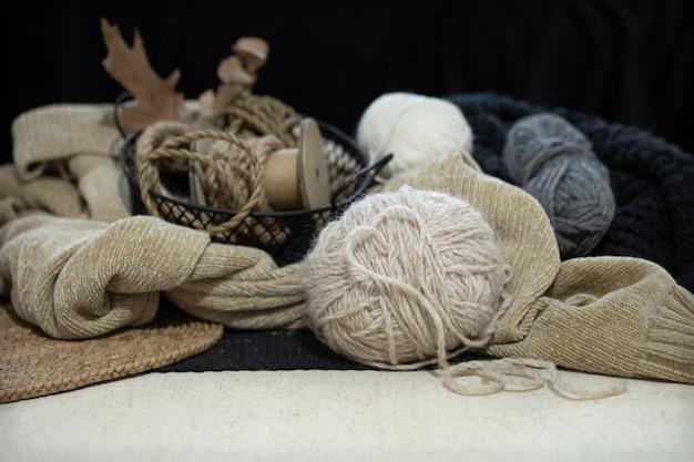 セーターと糸のスペースにある糸のボールのクローズアップの静物。糸でできたハート。