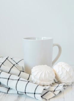 Натюрморт керамическая чашка с горячим напитком, сладкими конфетами и салфеткой на светлом фоне.