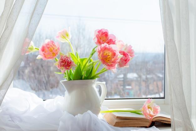 チューリップと窓に古い本のある花瓶の静物