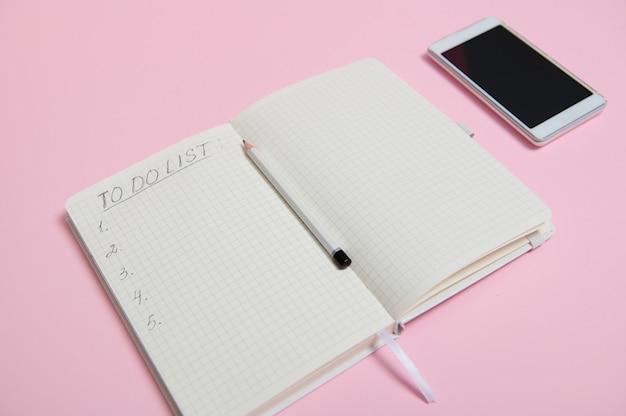 정물. 열린 의제, 일기, 복사 공간에 따라 흰색 종이에 할 일 목록이 있는 노트북 한가운데에 있는 연필 옆에 분홍색 배경에 누워 있는 흰색 휴대폰