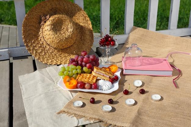 静物と食べ物の写真木の床の黄麻布の上に果物のプレートが立っています