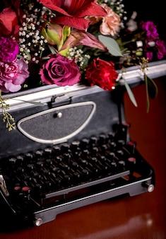 Натюрморт - старинный печатный станок и яркие цветы на темном фоне.
