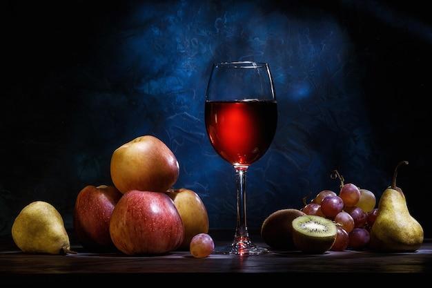 진한 파란색 배경에 정물화, 사과, 포도, 과일 및 빨간 주스. 다이어트, 건강한 식생활.