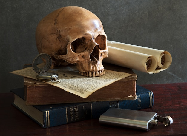 Still life art photography on human skull skeleton with book