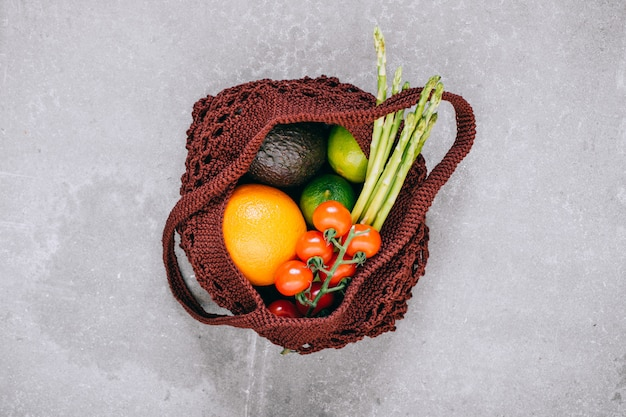 Still life of biodegradable shopping bag with raw vegetables on marble background