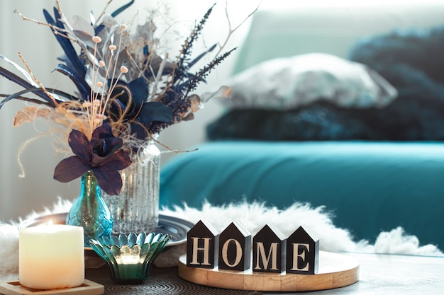 Still life in blue tones, with wooden inscription home and decorative elements in the living room.