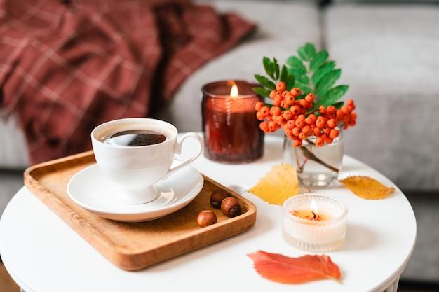 Натюрморт книга свеча ягода рябина и чашка чая или кофе в гостиной на столе дома