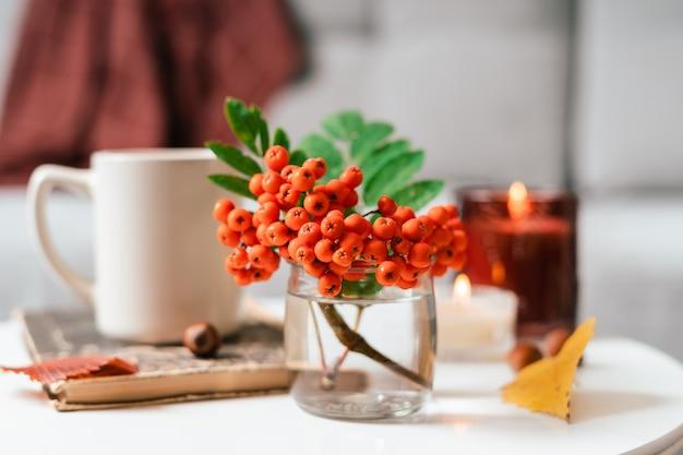 Натюрморт книга свеча ягода рябина и чашка чая или кофе в гостиной на столе дома Premium Фотографии