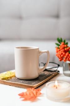 Натюрморт книга свеча рябина ягода и чашка чая или кофе в гостиной на столе дома