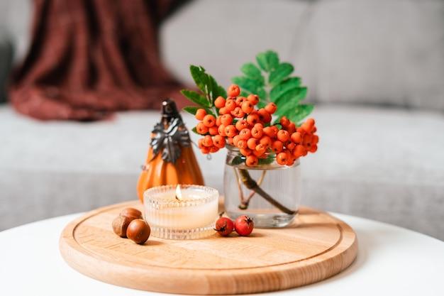 Натюрморт книга свеча рябина ягода тыква и чашка чая или кофе в гостиной на столе