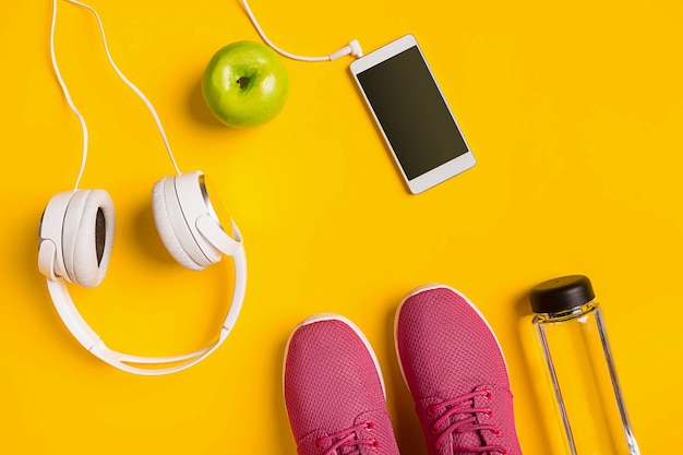 Still life of bottle with water, sportswear, apple on yellow background. top view, flat lay. sports and fitness background.