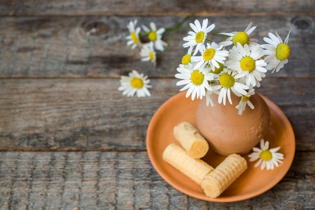 Still life of a bouquet of daisies in a vase and waffle tubes. wooden rustic style.