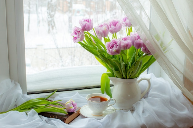 Still life a bouquet of lilac tulips in a vase a mug of tea an old book on the window