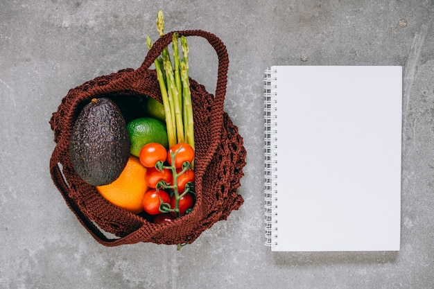Still life of brown biodegradable shopping bag with raw vegetables on gray