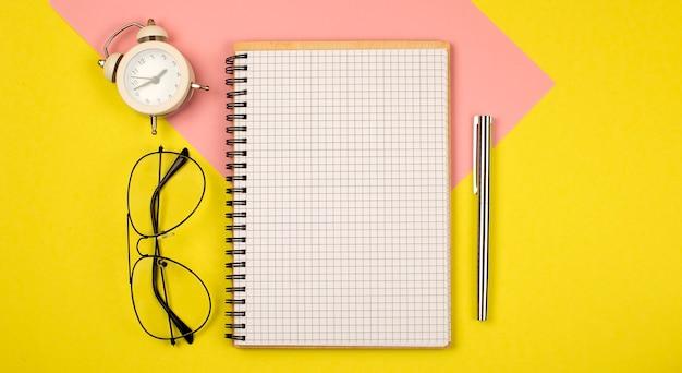 Натюрморт, бизнес, канцелярские товары, концепция образования: открытый блокнот с пустыми страницами на желтом фоне, вид сверху