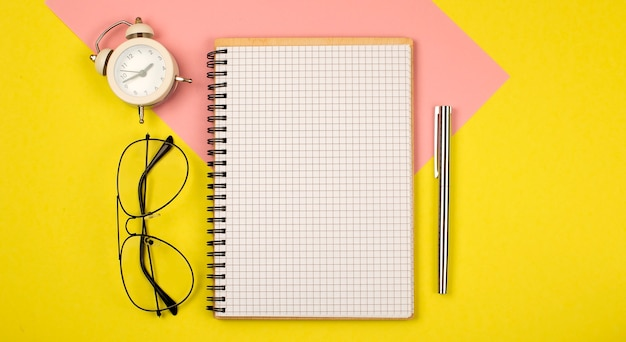 Still life, business, office supplies , education concept : top view open notebook with blank pages on yellow background