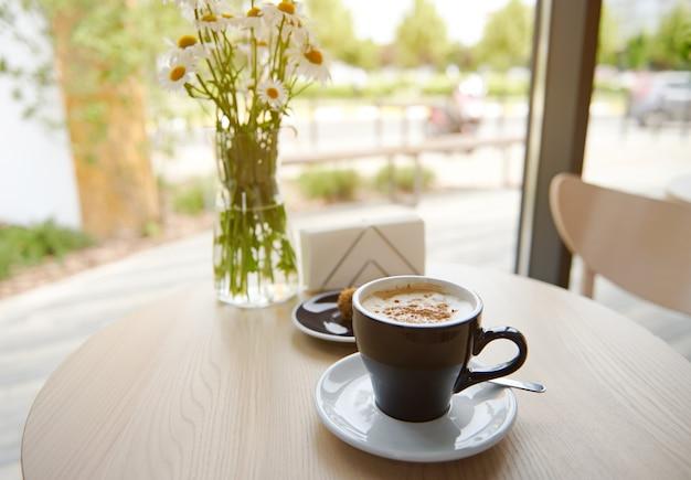 静物。通りの背景にあるカフェテリアの木製テーブルに青いセラミックカップのカプチーノ。大きな床の長さの窓から太陽光線がカフェに入ります。