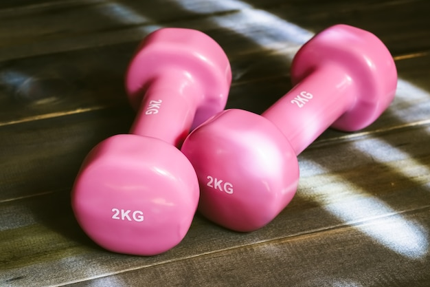 Still life close up of pink dumbbells  on wooden background
