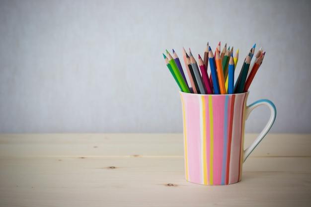 Цветные карандаши натюрморта в красочной чашке на деревянном столе - винтажная картина стиля влияния