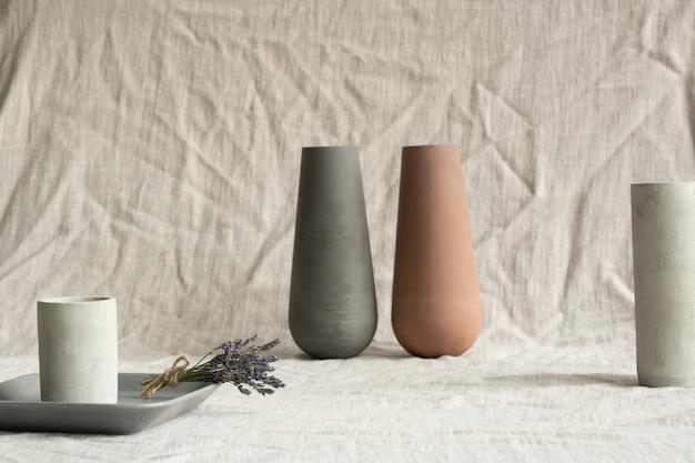 Натюрморт из двух глиняных ваз ручной работы, белых керамических стаканов, серого подноса с букетом сухой лаванды на льняной ткани.