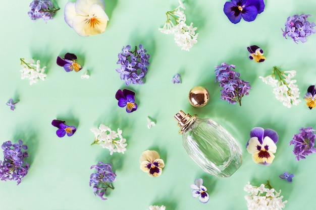 Still life, composition, set with fresh beautiful colorful flowers, fragrant and bottle with women's perfume. violets and lilacs. top view. flat lay.