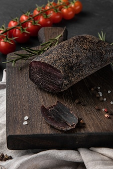 나무 커팅 보드, 측면보기, 세로 사진에 엘크 고기의 붉은 훈제 건조 햄 조각으로 정물화 구성